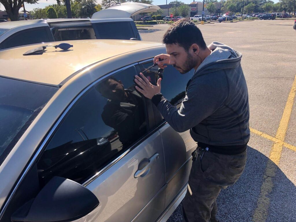 locksmith tech trying to open a car with his ACCESS tools services AIR JACK and pick tools in parking lot of walmart in Houston