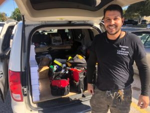 dan pinto owner of Houston key locksmith with uniform behind his mobile work car with locksmith tools, locks and keys