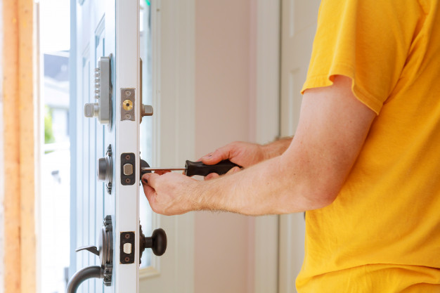 locksmith tech-installing-repairing-new-lock-on-a-door