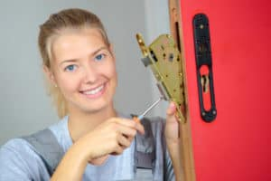 a locksmith women holding screw driver on commercial lock cylinder door